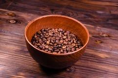 在碗的烤咖啡豆在木桌上 图库摄影