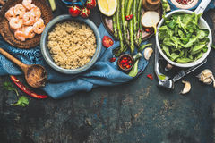在碗的煮熟的白色奎奴亚藜有烹调在黑暗的土气背景,顶视图,边界的新鲜蔬菜的成份 库存图片