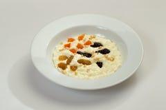 在碗的燕麦粥粥冠上了用葡萄和葡萄干 免版税库存照片