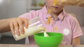 在碗的男小学生倾吐的牛奶用谷物,鲜美健康早餐,关闭 影视素材