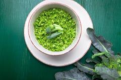 在碗的硬花甘蓝米在绿色背景 顶视图 顶上 复制空间 切细的硬花甘蓝 免版税库存照片