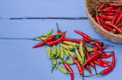 在碗的红色和绿色辣椒在木背景 库存图片