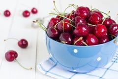 在碗的红色樱桃在蓝色毛巾的白色木背景 库存照片