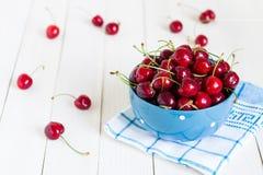 在碗的红色樱桃在蓝色毛巾的白色木背景 免版税库存照片