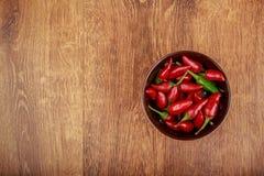 在碗的红辣椒在木桌上 图库摄影