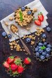在碗的自创muesli格兰诺拉麦片用在生锈的桌上的莓果 免版税库存照片