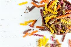 在碗的色的意大利fusilli面团在白色木桌上 库存图片