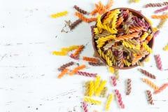 在碗的色的意大利fusilli面团在白色木桌上 免版税库存照片