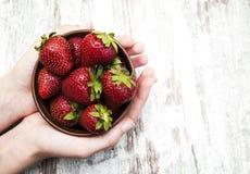 在碗的草莓用手 免版税图库摄影
