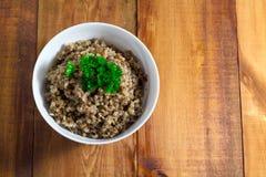 在碗的荞麦粥用在一个木背景特写镜头的荷兰芹 免版税库存图片