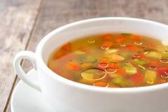 在碗的蔬菜汤在木头 图库摄影