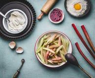 在碗的被剥皮的和切的大黄在与与烹调和烘烤的工具,顶视图的厨房用桌背景 季节性食物概念 库存图片