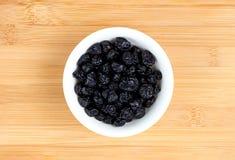 在碗的被脱水的蓝莓反对木头 免版税库存图片