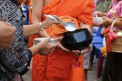 在碗的选择聚焦 泰国人投入食物给一个和尚`施舍在Songkran节日天滚保龄球的s 库存图片