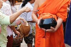 在碗的选择聚焦 泰国人投入食物给一个和尚`施舍在Songkran节日天滚保龄球的s 图库摄影