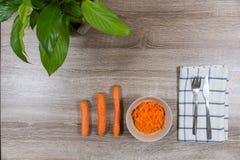 在碗的顶视图红萝卜沙拉和三棵红萝卜 免版税图库摄影