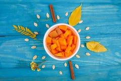 在碗的鲜美南瓜在蓝色背景 在倾吐的餐馆沙拉的主厨概念食物新鲜的厨房油橄榄 库存图片