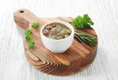在碗的鲜美蓬蒿调味汁用在白色木桌上的草本 免版税库存照片