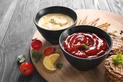 在碗的鲜美调味汁有在木板的快餐的 免版税库存图片