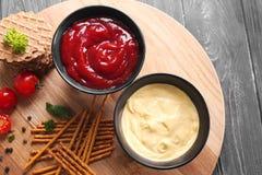 在碗的鲜美调味汁有在木板的快餐的 库存图片