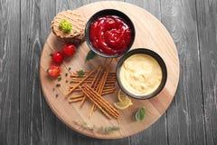 在碗的鲜美调味汁有在木桌上的快餐的 库存照片