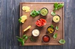 在碗的鲜美调味汁用在木板的草本 免版税库存图片