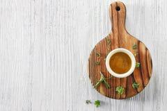 在碗的鲜美调味汁用在白色木桌上的草本 免版税库存图片