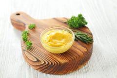 在碗的鲜美黄色调味汁用在白色木桌上的草本 免版税库存照片