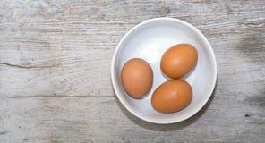 在碗的鸡蛋有老木背景 库存照片
