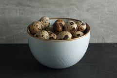 在碗的鹌鹑蛋在反对灰色背景的黑桌上 库存图片