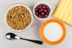 在碗,樱桃,餐巾,匙子,碗的Muesli用酸奶 免版税库存照片