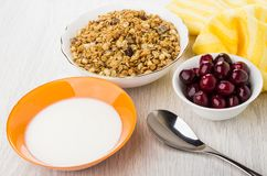 在碗,餐巾,樱桃,匙子,橙色碗的Muesli用酸奶 库存照片
