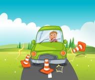 在碰撞交通锥体的一辆绿色汽车的男孩骑马 免版税图库摄影