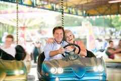 在碰撞用汽车的资深夫妇在游乐园 免版税图库摄影