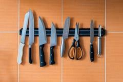 在磁铁持有人的刀子吊 橙色厨房墙壁 免版税库存照片