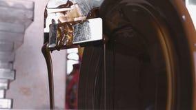 在磨炼机器的巧克力的温暖的液体巧克力 关闭上色百合软的查阅水 股票录像
