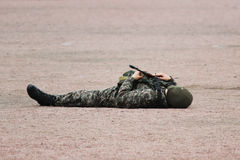 在示范pe期间,军事伪装衣物的人和说谎在他的面具在手中支持与机枪的沙子 图库摄影