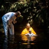 在礼拜式在水的洗礼浸没期间第一和多数重要基督徒奥秘,精神诞生的圣礼 库存图片