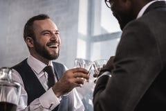 在礼服使叮当响的威士忌酒玻璃和谈话的商人 库存图片