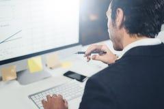 在礼服的确信的商人认为和与台式计算机一起使用在现代lightful办公室 水平 免版税图库摄影