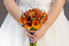 在礼服的背景的新娘的花束 库存照片