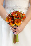 在礼服的背景的新娘的花束 免版税库存图片