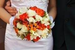 在礼服的背景的新娘的花束 图库摄影