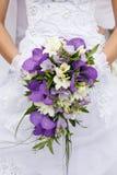在礼服的背景的新娘的花束 库存图片