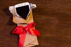在礼物包裹的智能手机 图库摄影