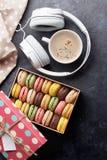在礼物盒和耳机的五颜六色的蛋白杏仁饼干 免版税库存图片