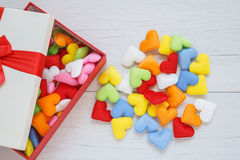 在礼物盒的五颜六色的心脏形状有在白色木pla的丝带的 免版税库存图片