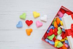 在礼物盒的五颜六色的心脏形状有在白色木pla的丝带的 库存图片