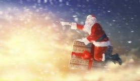 在礼物盒的圣诞老人飞行 免版税库存照片