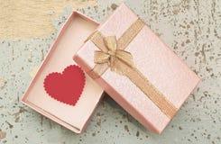 在礼物盒的红色心脏在难看的东西木头背景 库存图片